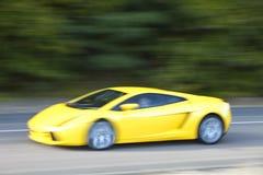 Gul bilkörning som är snabb på landsvägen Arkivfoton
