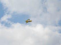 Gul biplan i flykten Royaltyfri Bild