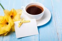 Gul blomma, kaffe och tomt kort på blå träbakgrund Arkivfoto