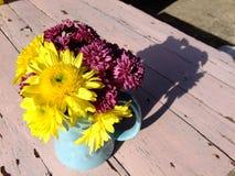 Gul blomma och violetblomma i exponeringsglas Arkivfoto