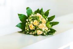 Gul blommabukett på den vita handtagstången arkivfoto