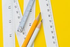 Gul blyertspenna och vita mäta band med cm och tum på det livliga gula lång eller tillverkareinstrumentet för bakgrund, för längd fotografering för bildbyråer