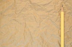 gul blyertspenna på en återanvänd skrynklig pappers- yttersida Royaltyfria Bilder