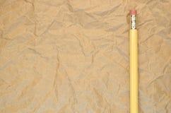 gul blyertspenna på en återanvänd skrynklig pappers- yttersida Arkivbild