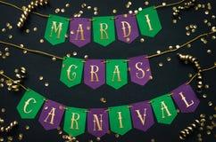 Gul bokstäver för Mardi Gras karneval på pappers- handgjord gräsplan och den purpurfärgade festliga girlanden, svart bakgrund Fer royaltyfri bild