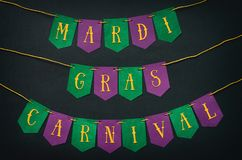 Gul bokstäver för Mardi Gras karneval på pappers- handgjord gräsplan och den purpurfärgade festliga girlanden, svart bakgrund Fer fotografering för bildbyråer