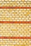Gul brickwall med röda band Arkivbild