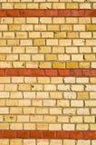 Gul brickwall med röda band Royaltyfria Bilder