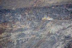 Gul bulldozer på svart vulkanisk jord Royaltyfria Foton