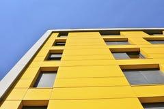 Gul byggnad med fönster och blå himmel Arkivfoton