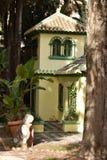 Gul fasad mellan dungen och den gröna trädgården och krukorna arkivbilder