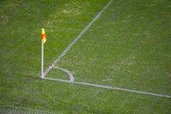 Gul flagga i hörnet av fotbolllekplatsen, lat blåsa för vind Arkivbild