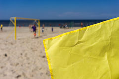 Gul flagga på ett fotbollfält på stranden Royaltyfri Fotografi