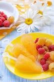 Gul fruktglass av gula hallon på en platta på bakgrunden av tusenskönor Arkivfoton