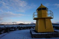 Gul fyr på kusten med berg bakom royaltyfri fotografi