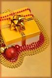 Gul gåvaask med julbaubles och pärlor Royaltyfria Bilder