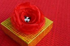 Gul gåvaask med rött slut för tygblommagarnering upp royaltyfri foto