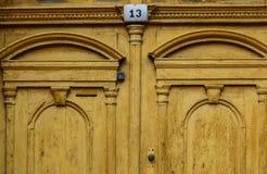 Gul gammal dörr med nummer 13 Arkivfoto