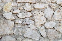 Gul gammal forntida fallfärdig vägg med kors sned naturliga naturliga stenar, kullersten med cementerade sömmar och kopieringsutr Fotografering för Bildbyråer