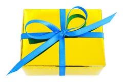 Gul glansig gåva som slås in gåva med den blåa satängpilbågen Fotografering för Bildbyråer