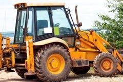 Gul grävskopa, bulldozermaskin och arbetartraktor arbeten för väg för konstruktionsdikeinstallation Vägmaskineri på konstruktions Royaltyfria Foton