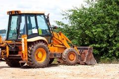 Gul grävskopa, bulldozermaskin och arbetartraktor arbeten för väg för konstruktionsdikeinstallation Vägmaskineri på konstruktions Fotografering för Bildbyråer