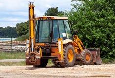 Gul grävskopa, bulldozermaskin och arbetartraktor arbeten för väg för konstruktionsdikeinstallation Vägmaskineri på konstruktions Royaltyfria Bilder