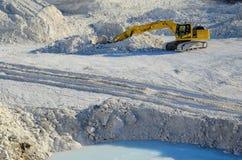 Gul grävskopa i kalkstenvillebråd Arkivfoton
