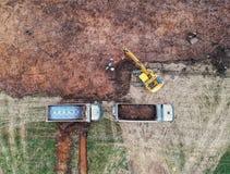 Gul grävskopa och lastbilar royaltyfri foto
