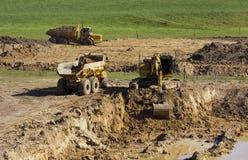 Gul grävskopa och stora gula lastbilar Arkivbild
