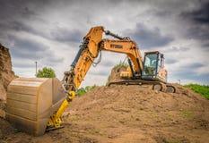 Gul grävskopa på arbete royaltyfria foton