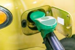 Gul guld- bil på en bensinstation som fylls med bränsle royaltyfri foto