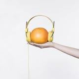 Gul hörlurar på apelsinen Royaltyfri Fotografi