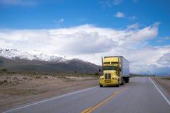 Gul halv lastbil med släpet på vägen med det snöig berget Arkivbild