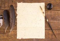 Gul hand - den gjorda papper och fjäderpennan på lantligt uppvaktar arkivbilder