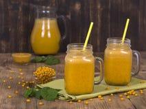Gul hav-buckthorn fruktsaft i ett exponeringsglas och en mogen Yellow Sea buckthorn på tappningträtabellen Bio sund mat och drink Arkivbilder