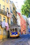 Gul historisk spårvagn i Lissabon som kör till och med den gamla staden av alfamaen arkivfoton