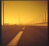 Gul huvudväg på solnedgången Arkivfoton