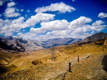 Gul jord och klara berg arkivbilder