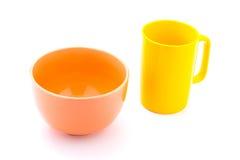 Gul kaffekopp och orange bunke Arkivfoto