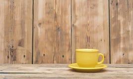 Gul kaffekopp och tefat Arkivfoton