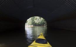 Gul kajak som går inom en tunnel Arkivbild