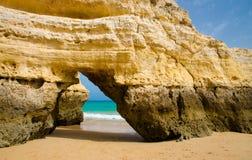 Gul kalkstenbåge på den guld- sandiga stranden, Portimao stad, Portugal royaltyfri bild