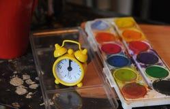 Gul klocka och en olje- färg Arkivfoton