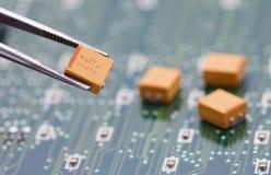 Gul kondensator för hacka med plattång royaltyfria bilder