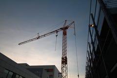 Gul konstruktionskran som omges av lättheter Fotografering för Bildbyråer