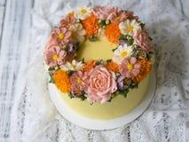 Gul kräm- kaka som dekoreras med buttercreamblommor - pioner, rosor, krysantemum, scabiosaen, nejlikor - på vit träbaksida royaltyfri foto