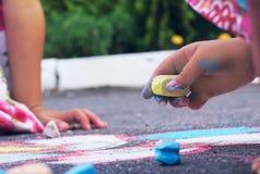 Gul krita i händerna av en flickateckning på asfalten Barnet som tecknar en krita på asfalt arkivbilder