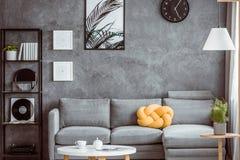Gul kudde på grå soffa royaltyfri fotografi
