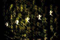 Gul kupidonbokeh i mörkret Arkivbild